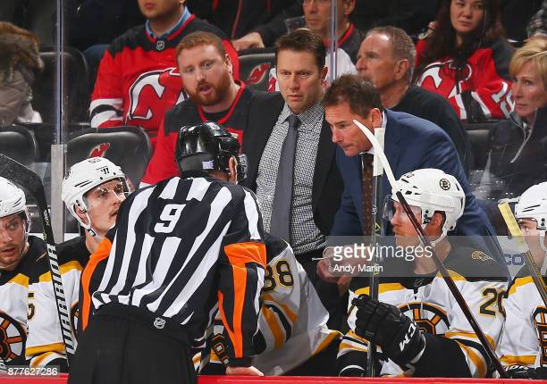 Head coach Bruce Cassidy of the Boston Bruins talks with referee Dan O'Rourke against the New Jersey Devils during the game at Prudential Center on...