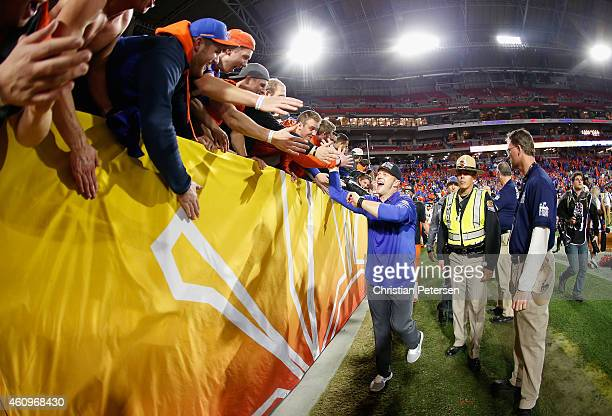 Head coach Bryan Harsin of the Boise State Broncos celebrates with fans after defeating the Arizona Wildcats 3830 to win the Vizio Fiesta Bowl at...