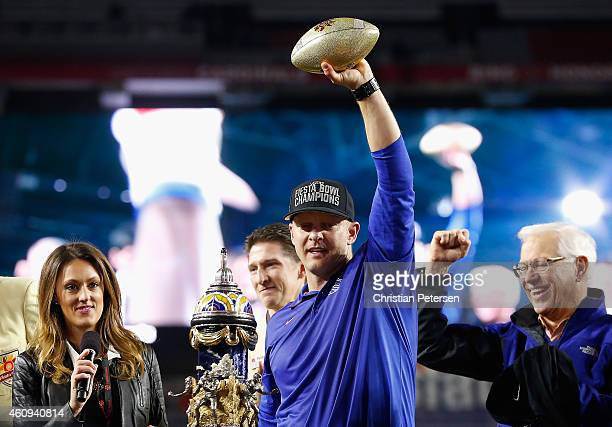 Head coach Bryan Harsin of the Boise State Broncos holds up the Vizio Fiesta Bowl trophy in celebration after defeating the Arizona Wildcats 3830 at...