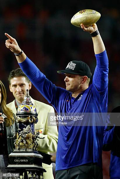 Head coach Bryan Harsin of the Boise State Broncos points to the crowd as he holds up the Fiesta Bowl trophy after the team's 3830 victory over the...