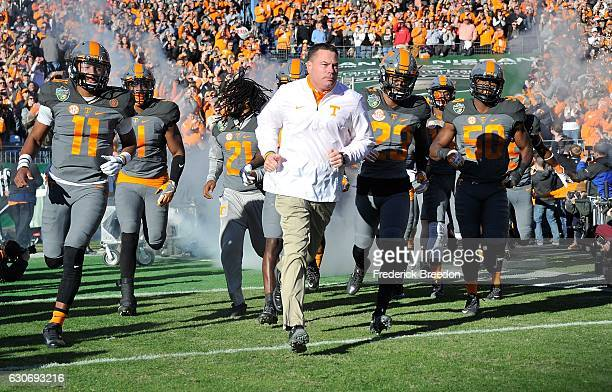 Head coach Butch Jones and quarterback Joshua Dobbs rush out onto the field prior the Franklin American Mortgage Music City Bowl against the Nebraska...
