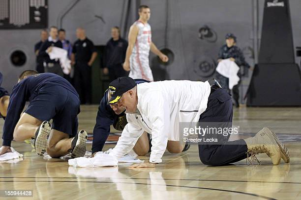 Head coach Buzz Williams of the Marquette Golden Eagles helps dry condensation off of the court which caused the start of their game against the Ohio...