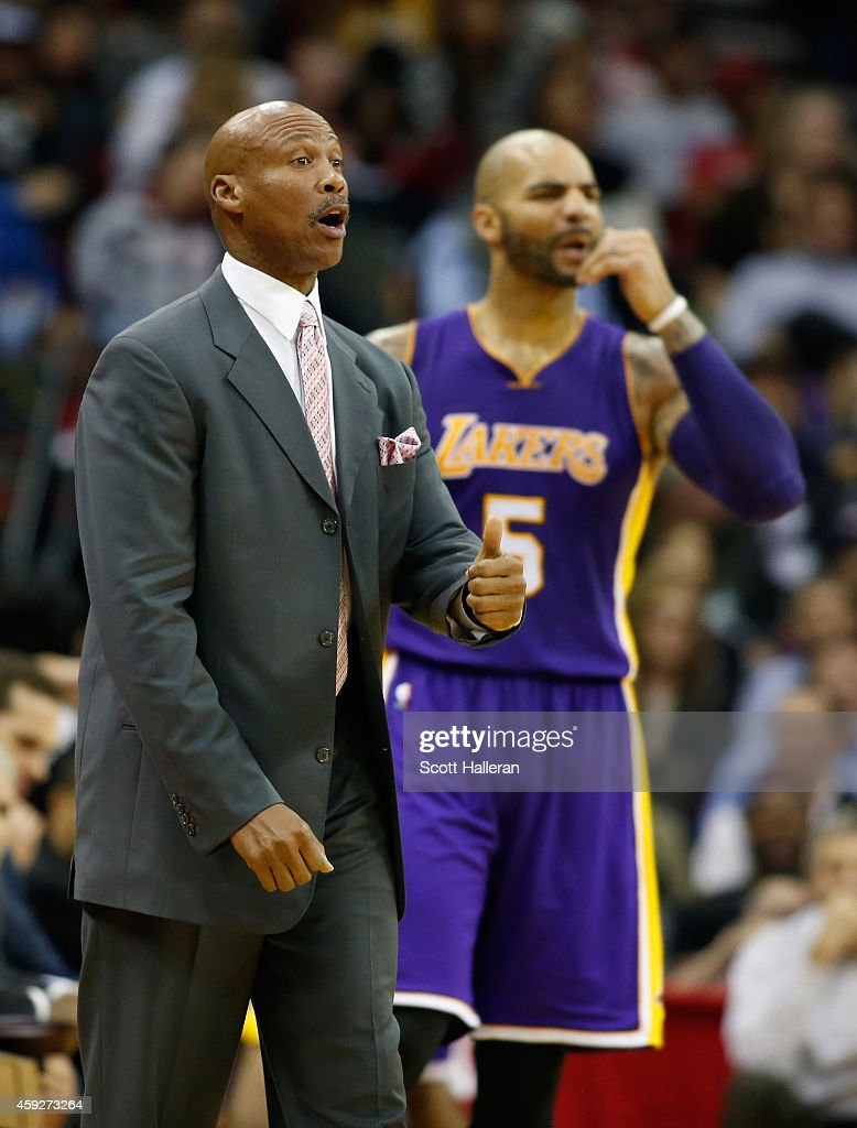 Head coach Byron Scott of the Los Angeles Lakers waits on the court alongside Carlos Boozer #5 during their game against the Houston Rockets at the Toyota Center on November 19, 2014 in Houston, Texas.