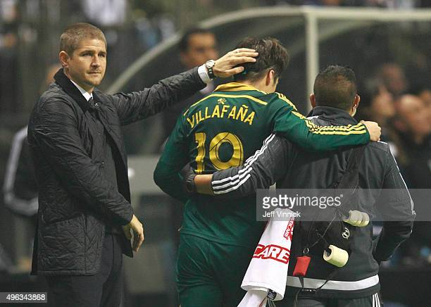 Head coach Carl Robinson of the Vancouver Whitecaps FC comforts Jorge Villafana of the Portland Timbers as he is helped off the field after an injury...