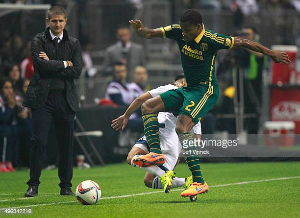 Head coach Carl Robinson of the Vancouver Whitecaps FC looks on as Nat Borchers of the Portland Timbers beats Nicolas Mezquida of the Vancouver...