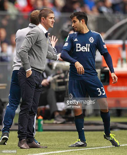 Head coach Carl Robinson of the Vancouver Whitecaps FC talks to Steven Beitashour during their MLS game against the Colorado Rapids April 5 2014 in...