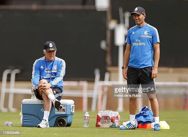 Head coach Carlo Ancelotti and his assistant Zinedine Zidane of Real Madrid follow their players during a training session at UCLA Campus on July 30...