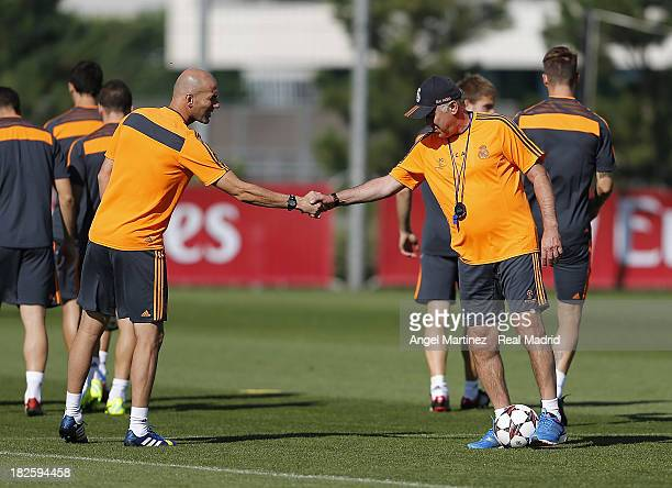 Head coach Carlo Ancelotti and his assistant Zinedine Zidane of Real Madrid shake hands during a training session ahead of their UEFA Champions...