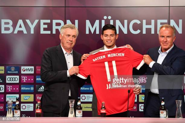 Head coach Carlo Ancelotti and KarlHeinz Rummenigge CEO of FC Bayern Muenchen present James Rodriguez with his new jersey during a press conference...
