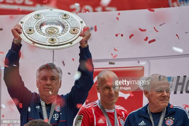 Head coach Carlo Ancelotti of Bayern Muenchen poses with the Championship trophy in celebration of the 67th German Championship title following...