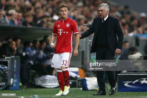 Head coach Carlo Ancelotti of Muenchen leads substitute Joshua Kimmich back to the bench during the UEFA Champions League Quarter Final first leg...