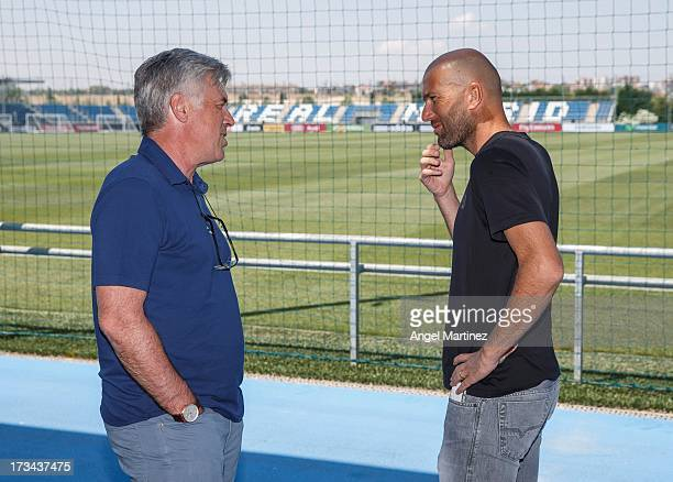 Head coach Carlo Ancelotti of Real Madrid chats with his assistant Zinedine Zidane at Valdebebas training ground on July 14 2013 in Madrid Spain