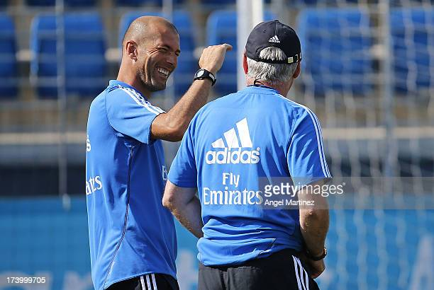 Head coach Carlo Ancelotti of Real Madrid chats with his assistant Zinedine Zidane during a training session at Valdebebas training ground on July 19...