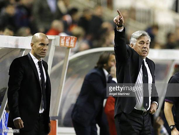 Head coach Carlo Ancelotti of Real Madrid gives instructions beside his assistant Zinedine Zidane during the La Liga match between Rayo Vallecano and...