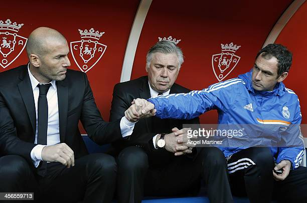 Head coach Carlo Ancelotti of Real Madrid looks on as his assistants Zinedine Zidane and Paul Clement shake hands during the La Liga match between CA...