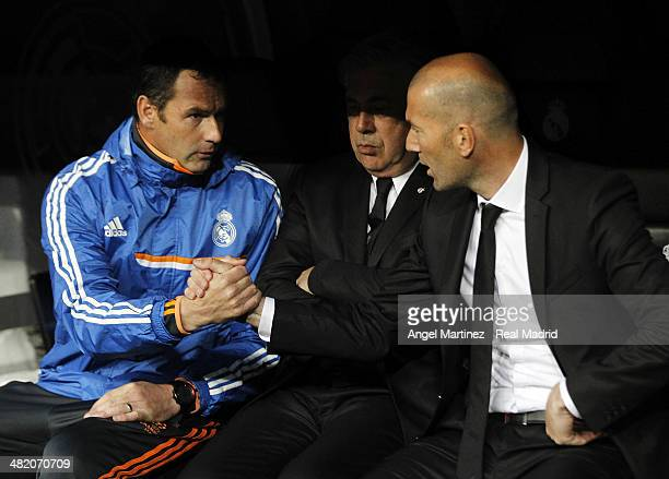Head coach Carlo Ancelotti of Real Madrid looks on as his assistants Paul Clement and Zinedine Zidane shake hands before the UEFA Champions League...