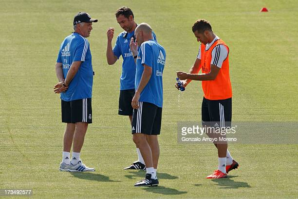 Head coach Carlo Ancelotti of Real Madrid talks with assistant coach Zinedine Zidane and a member of his phisical staff during his first training...