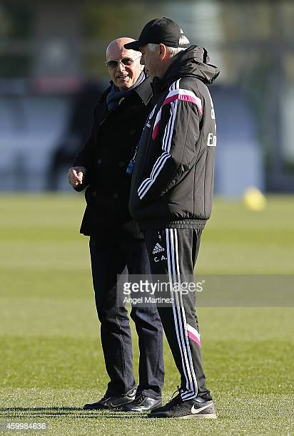 Head coach Carlo Ancelotti of Real Madrid talks with former Italian coach Arrigo Sacchi during a training session at Valdebebas training ground on...