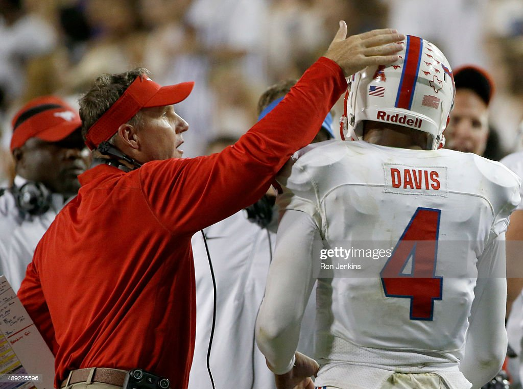 Head coach Chad Morris of the Southern Methodist Mustangs welcomes Matt Davis #4 back to the bench after Davis scored a touchdown against the TCU Horned Frogs in the third quarter at Amon G. Carter Stadium on September 19, 2015 in Fort Worth, Texas.