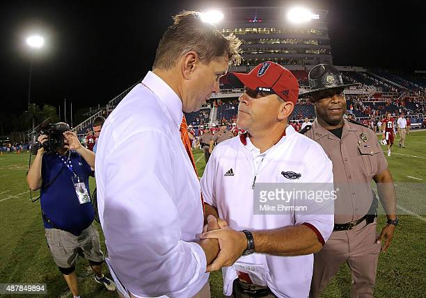 Head coach Charlie Partridge of the Florida Atlantic Owls shakes hands with Al Golden head coach of the Miami Hurricanes during a game at FAU Stadium...