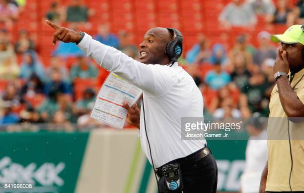 Head coach Charlie Strong of the South Florida Bulls yells instructions to his team on the field during the game against the Stony Brook Sea Wolves...