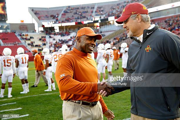 Head coach Charlie Strong of the Texas Longhorns and head coach Paul Rhoads of the Iowa State Cyclones shake hands at the fifty yard line during...