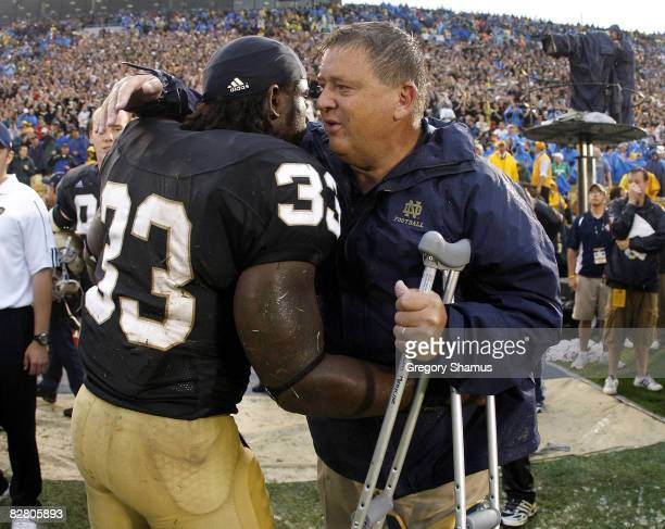 Head coach Charlie Weis of the Notre Dame Fighting Irish is congratulated by Robert Hughes during the final seconds of their 3517 victory over the...