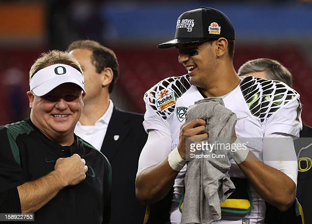 Head coach Chip Kelly celebrates with Marcus Mariota of the Oregon Ducks after their 35 to 17 win over the Kansas State Wildcats in the Tostitos...