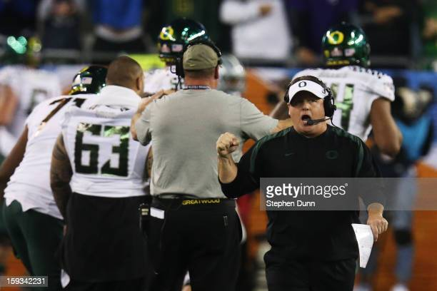 Head coach Chip Kelly of the Oregon Ducks celebrates a third quarter touchdown against the Kansas State Wildcats during the Tostitos Fiesta Bowl at...
