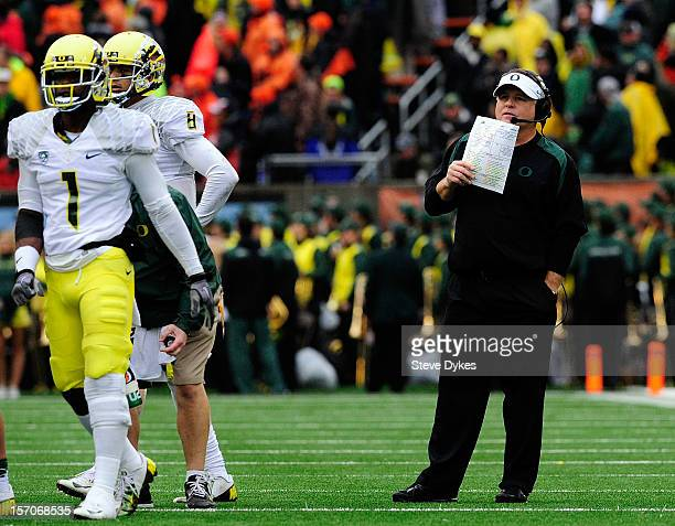 Head coach Chip Kelly of the Oregon Ducks speaks with wide receiver Josh Huff and quarterback Marcus Mariota of the Oregon Ducks in the third quarter...