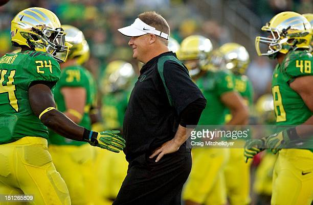 Head coach Chip Kelly of the Oregon Ducks talks to Kenjon Barner during warm ups against the Arkansas State Red Wolves on September 1, 2012 at Autzen...