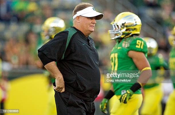 Head coach Chip Kelly of the Oregon Ducks watches warm ups against the Arkansas State Red Wolves on September 1, 2012 at Autzen Stadium in Eugene,...