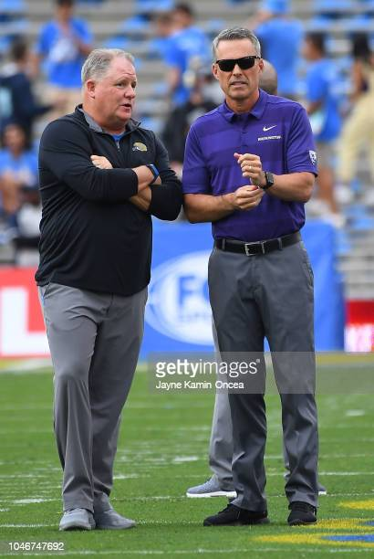 Head coach Chip Kelly of the UCLA Bruins and head coach Chris Petersen of the Washington Huskies look as players warm up for the game on October 6...