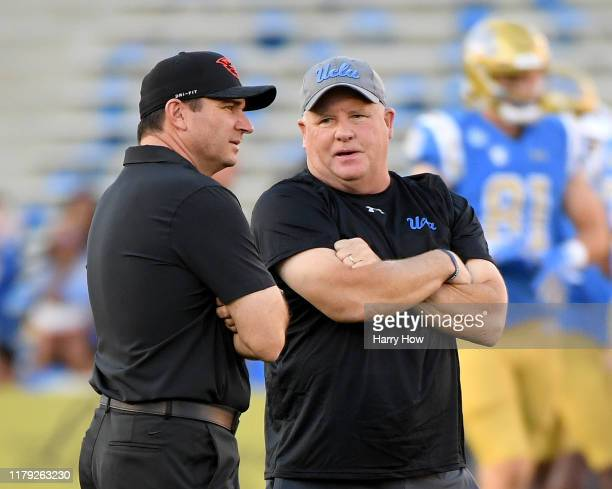 Head coach Chip Kelly of the UCLA Bruins and head coach Jonathan Smith of the Oregon State Beavers talk on the field as their teams warm up before...