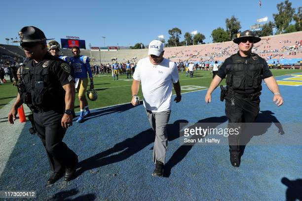 Head coach Chip Kelly of the UCLA Bruins is escorted off the field after the San Diego State Aztecs defeated UCLA Bruins 23-14 in a game on September...