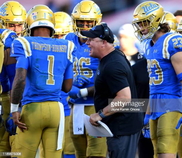 Head coach Chip Kelly talks with quarterback Dorian Thompson-Robinson of the UCLA Bruins during a time out in the game against the USC Trojans at the...