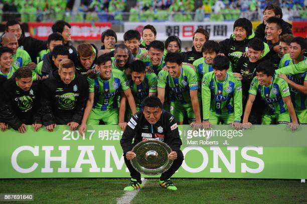 Head coach Cho Kwi Jae of Shonan Bellmare lifts the trophy as they celerbrate J2 champions and promotion to J1 after the JLeague J2 match between...