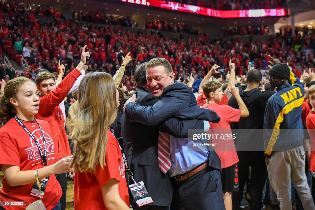 Head coach Chris Beard of the Texas Tech Red Raiders hugs assistant coach Mark Adams after his team defeated the West Virginia Mountaineers 72-71 on January 13, 2018 at United Supermarket Arena in Lubbock, Texas.