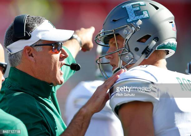 Head coach Chris Creighton of the Eastern Michigan Eagles talks with his quarterback Brogan Roback against the Rutgers Scarlet Knights during the...