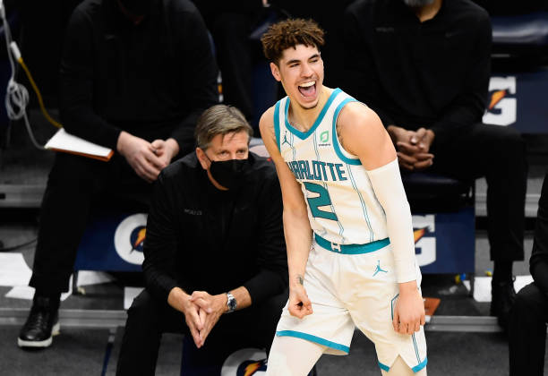 Head coach Chris Finch of the Minnesota Timberwolves looks on as LaMelo Ball of the Charlotte Hornets celebrates a three-point basket during the...