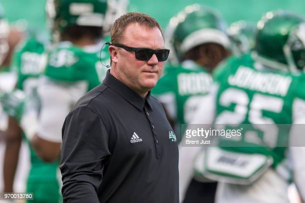 Head coach Chris Jones of the Saskatchewan Roughriders on the field during warmup before the preseason game between the Calgary Stampeders and...
