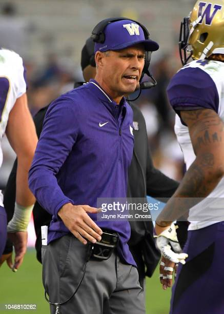 Head coach Chris Petersen of the Washington Huskies congratulates players after a touchdown in the first half of the game against the UCLA Bruins at...