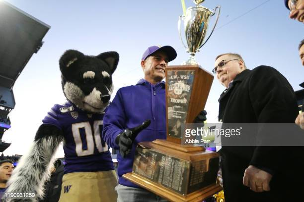 Head Coach Chris Petersen of the Washington Huskies holds the Apple Cup trophy after defeating the Washington State Cougars 3113 during their game at...