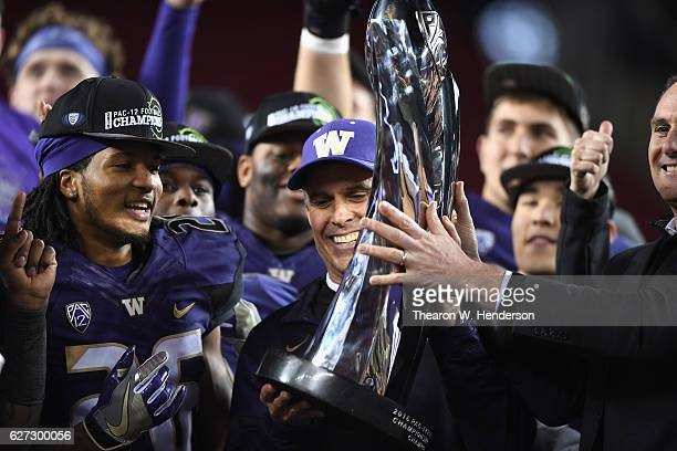 Head coach Chris Petersen of the Washington Huskies is awarded the Pac12 Championship game trophy after they beat the Colorado Buffaloes at Levi's...