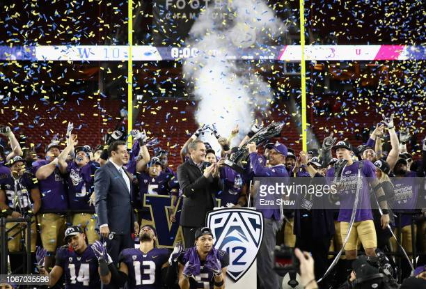 Head coach Chris Petersen of the Washington Huskies is given the championship trophy after the Huskies beat the Utah Utes to win the Pac 12...