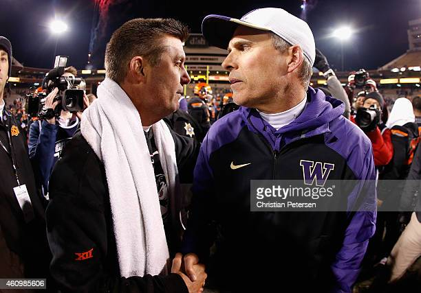 Head coach Chris Petersen of the Washington Huskies shakes hands with Mike Gundy of the Oklahoma State Cowboys following the TicketCity Cactus Bowl...