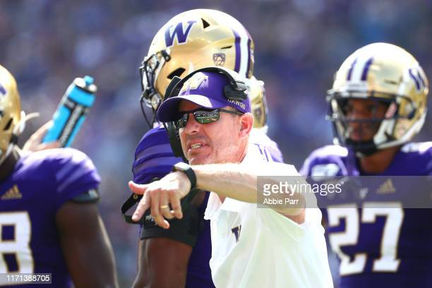 Head Coach Chris Petersen of the Washington Huskies signals to team members in the first quarter against the Eastern Washington Eagles during their...