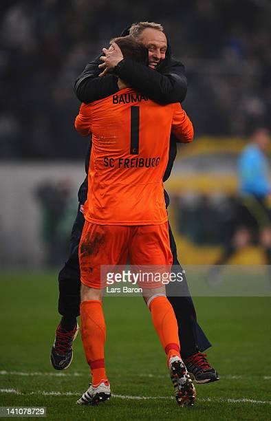 Head coach Christian Streich of Freiburg celebrates with goalkeeper Oliver Baumann after the Bundesliga match between Borussia Moenchengladbach and...