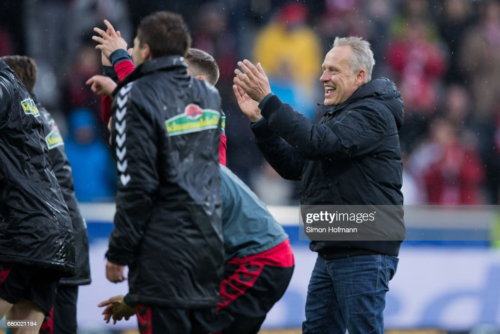 Head coach Christian Streich of Freiburg (R) joins his team to celebrate victory after the Bundesliga match between SC Freiburg and FC Schalke 04 at Schwarzwald-Stadion on May 7, 2017 in Freiburg im Breisgau, Germany.