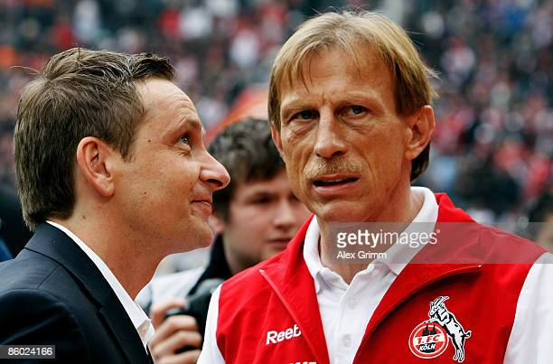 Head coach Christoph Daum of Koeln chats with manager Horst Heldt of Stuttgart before the Bundesliga match between 1FC Koeln and VfB Stuttgart at the...